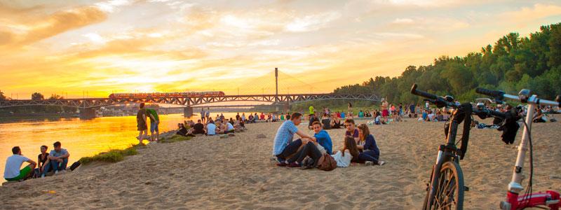 Grupki znajomych siedzą na plaży nad Wisłą o zachodzie słońca.