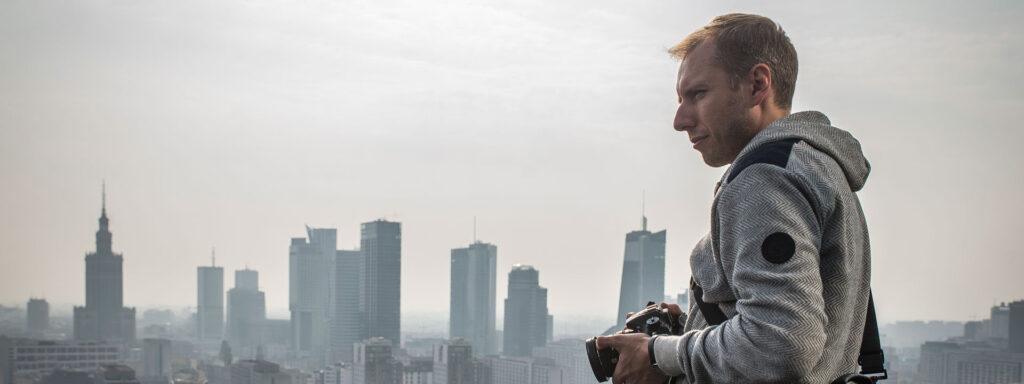 Fotograf ogląda panoramę miasta z dachu wieżowca